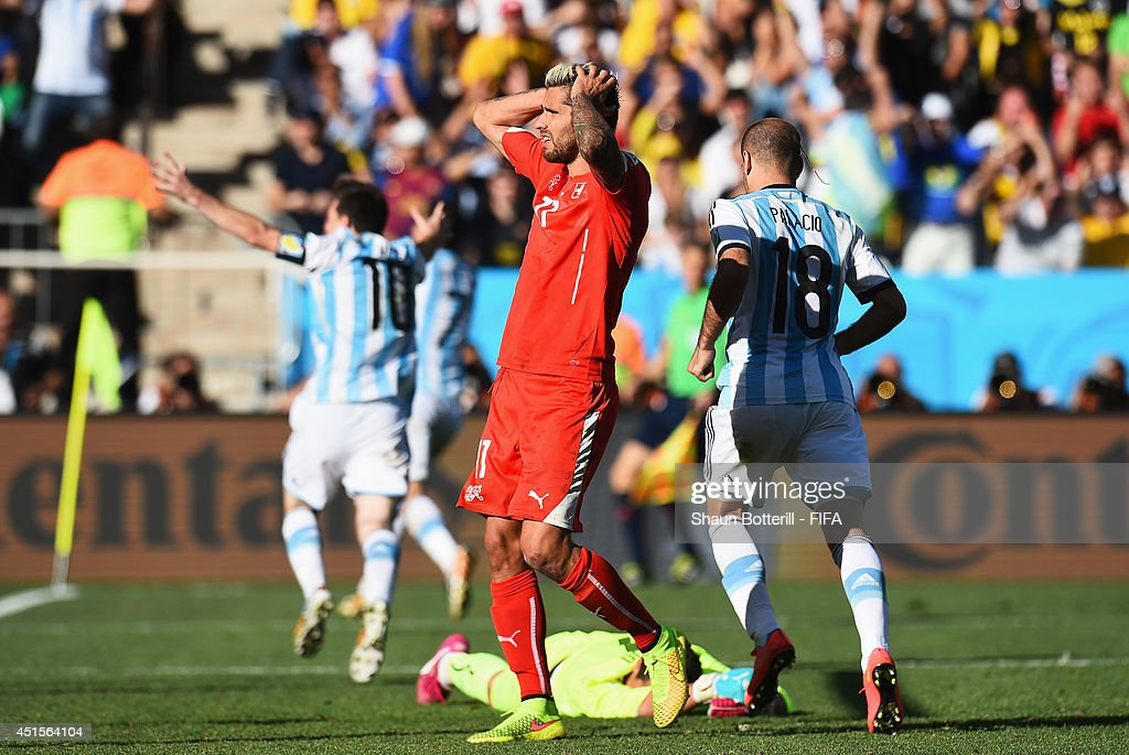 <a gi-track='captionPersonalityLinkClicked' href=/galleries/search?phrase=Valon+Behrami&family=editorial&specificpeople=453450 ng-click='$event.stopPropagation()'>Valon Behrami</a> (C) of Switzerland reacts after conceding the first goal to Argentina during the 2014 FIFA World Cup Brazil Round of 16 match between Argentina and Switzerland at Arena de Sao Paulo on July 1, 2014 in Sao Paulo, Brazil.