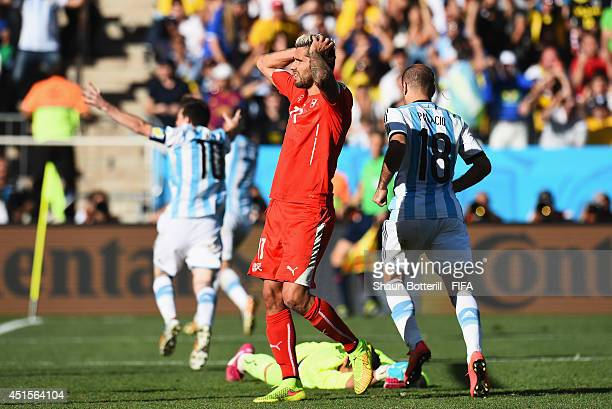 Valon Behrami of Switzerland reacts after conceding the first goal to Argentina during the 2014 FIFA World Cup Brazil Round of 16 match between...