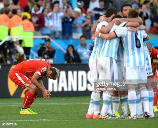 Valon Behrami of Switzerland reacts as Argentina's players celebrate after a goal scored by Di Maria during the 2014 FIFA World Cup Round of 16...