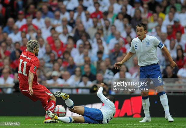 Valon Behrami of Switzerland tackles Ashley Cole of England during the UEFA EURO 2012 Group G qualifying match between England and Switzerland at...