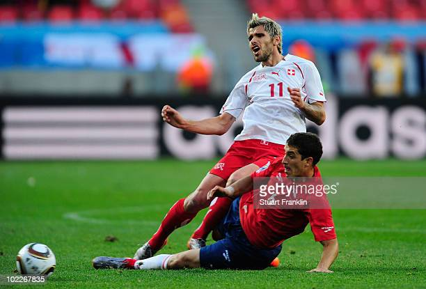Valon Behrami of Switzerland tackles Carlos Carmona of Chile during the 2010 FIFA World Cup South Africa Group H match between Chile and Switzerland...