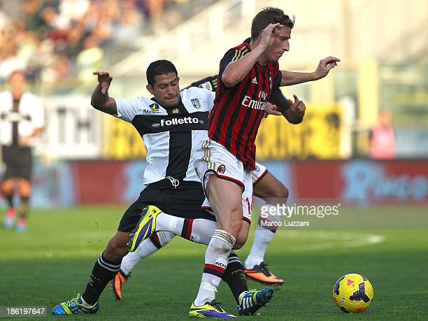 Valter Birsa of AC Milan competes for the ball with Walter Gargano of Parma FC during the Serie A match between Parma FC and AC Milan at Stadio Ennio...