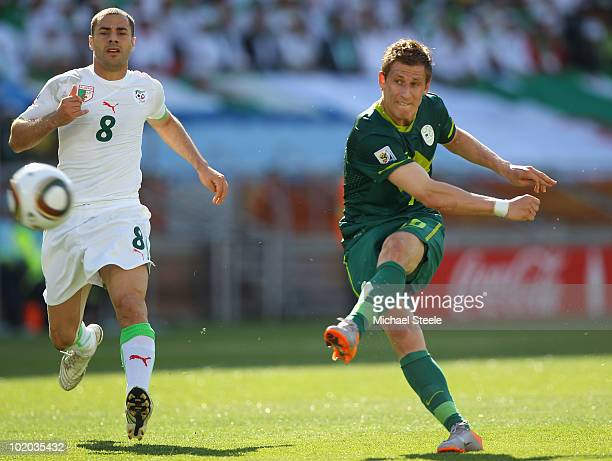 Valter Birsa of Slovenia shoots as Medhi Lacen looks on during the 2010 FIFA World Cup South Africa Group C match between Algeria and Slovenia at the...