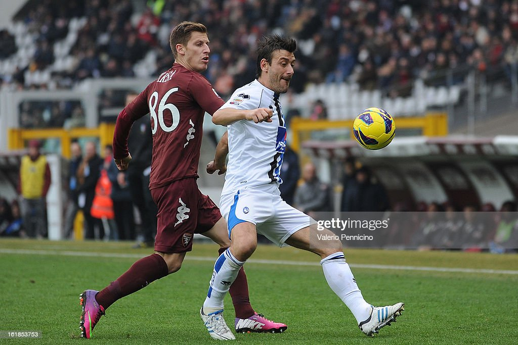 Valter Birsa (L) of Torino FC competes with Gianpaolo Bellini of Atalanta BC during the Serie A match between Torino FC and Atalanta BC at Stadio Olimpico di Torino on February 17, 2013 in Turin, Italy.