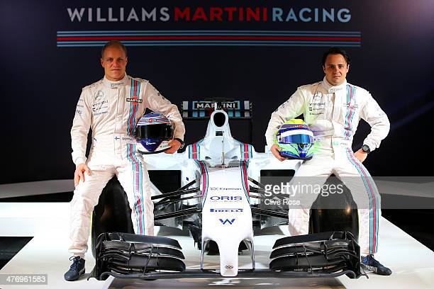 Valtteri Bottas of Finland and Felipe Massa of Brazil pose with the Williams Martini Racing formula one car on March 6 2014 in London England