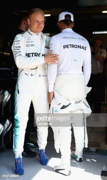 Valtteri Bottas of Finland and Mercedes GP and Lewis Hamilton of Great Britain and Mercedes GP talk in the garage during practice for the Formula One...