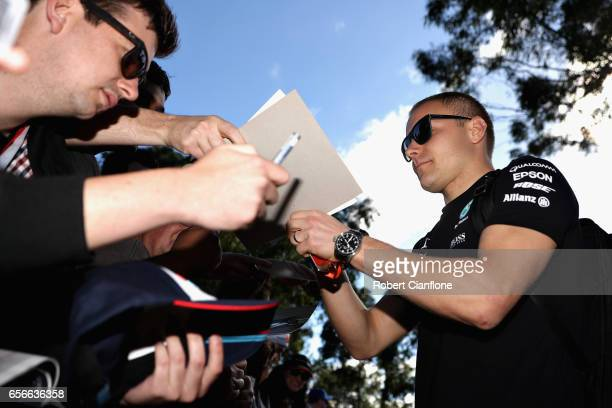 Valtteri Bottas of Finland and Mercedes GP arrives at the circuit and signs autographs for fans during previews to the Australian Formula One Grand...
