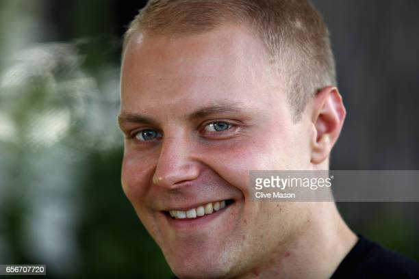Valtteri Bottas of Finland and Mercedes GP talks to the media in the Paddock during previews to the Australian Formula One Grand Prix at Albert Park...