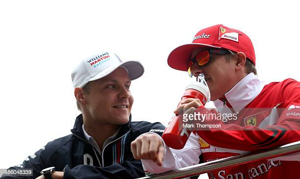 Valtteri Bottas of Finland and Williams and Kimi Raikkonen of Finland and Ferrari take part in the drivers parade prior to the Chinese Formula One...