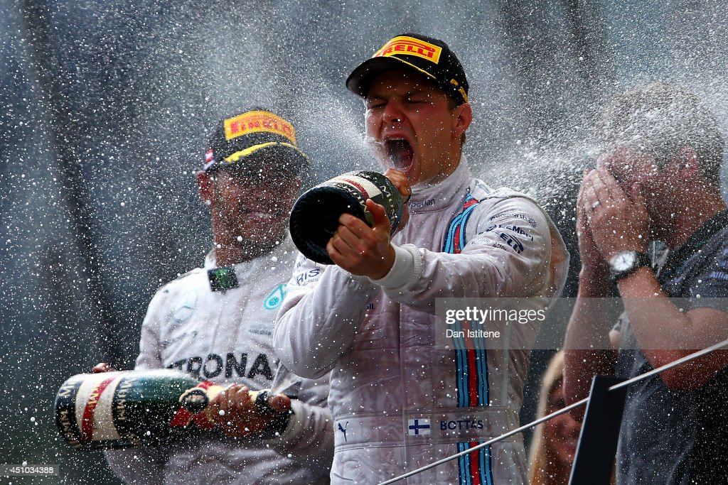 <a gi-track='captionPersonalityLinkClicked' href=/galleries/search?phrase=Valtteri+Bottas&family=editorial&specificpeople=8640136 ng-click='$event.stopPropagation()'>Valtteri Bottas</a> of Finland and Williams celebrates on the podium next to <a gi-track='captionPersonalityLinkClicked' href=/galleries/search?phrase=Lewis+Hamilton+-+Racecar+Driver&family=editorial&specificpeople=586983 ng-click='$event.stopPropagation()'>Lewis Hamilton</a> of Great Britain and Mercedes GP after finishing third in the Austrian Formula One Grand Prix at Red Bull Ring on June 22, 2014 in Spielberg, Austria.