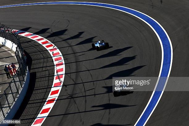Valtteri Bottas of Finland driving the Williams Martini Racing Williams FW38 Mercedes PU106C Hybrid turbo ahead of Lewis Hamilton of Great Britain...