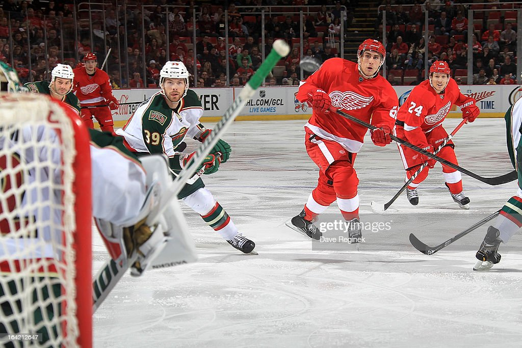 Valtteri Filppula #51 of the Detroit Red Wings and Nate Prosser #39 of the Minnesota Wild watch as the puck is shot towards the net during a NHL game at Joe Louis Arena on March 20, 2013 in Detroit, Michigan.
