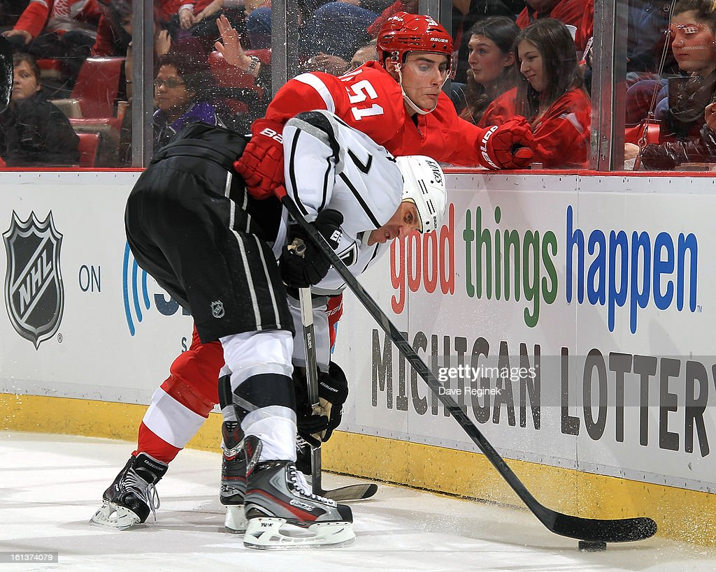Valtteri Filppula #51 of the Detroit Red Wings and Rob Scuderi #7 of the Los Angeles Kings battle on the boards for the puck during a NHL game at Joe Louis Arena on February 10, 2013 in Detroit, Michigan.