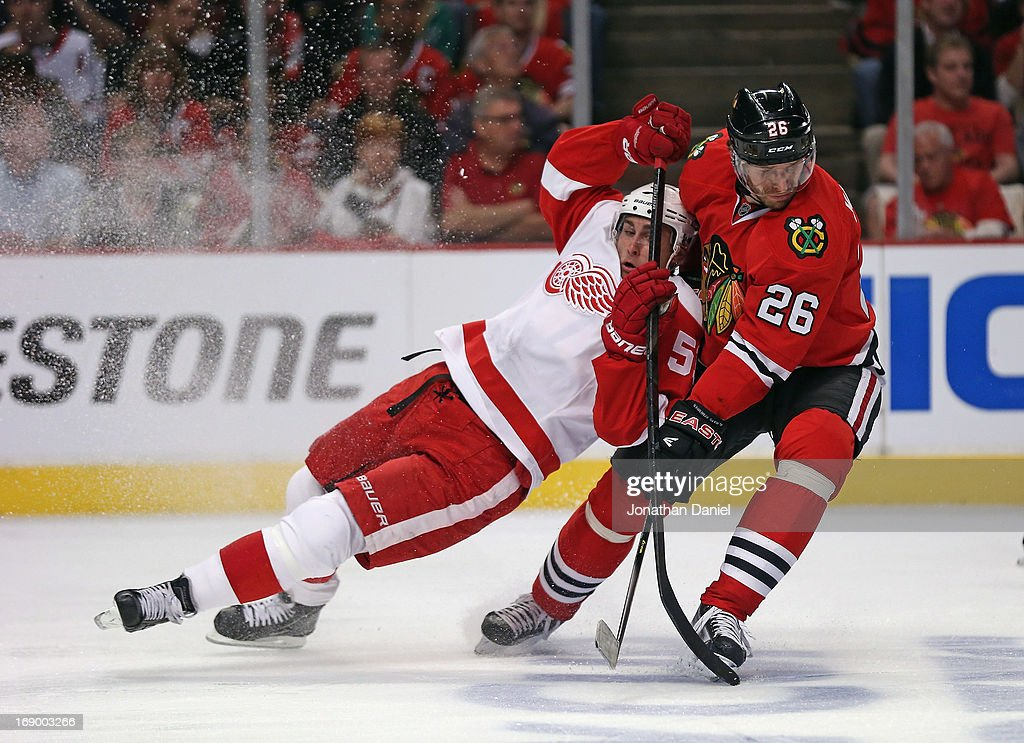 Valtteri Filppula of the Detroit Red Wings collides with Michal Handzus of the Chicago Blackhawks as they battle for the puck in Game Two of the...