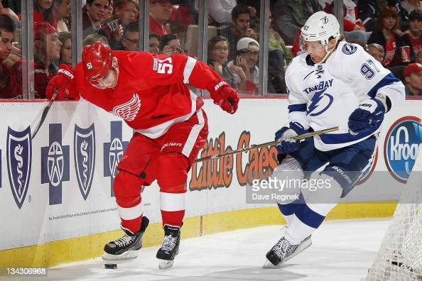 Valtteri Filppula of the Detroit Red Wings controls the puck with his skate while Matt Gilroy of the Tampa Bay Lightning reaches after during an NHL...