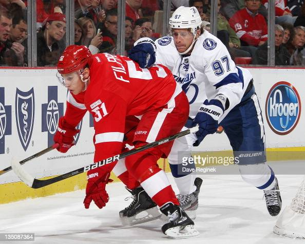 Valtteri Filppula of the Detroit Red Wings gets held up by Matt Gilroy of the Tampa Bay Lightning during an NHL game at Joe Louis Arena on November...