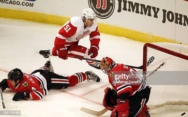 Valtteri Filppula of the Detroit Red Wings jumps over Niklas Hjalmarsson of the Chicago Blackhawks after scoring the winning goal against Marty Turco...