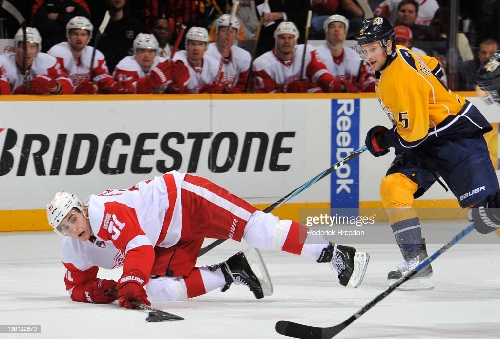 Valtteri Filppula of the Detroit Red Wings plays the puck from his knees in front of Blake Geoffrion of the Nashville Predators at the Bridgestone...