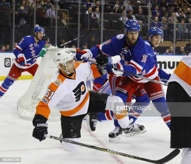 Valtteri Filppula of the Philadelphia Flyers is moved out of the crease by Tanner Glass of the New York Rangers during the first period at Madison...