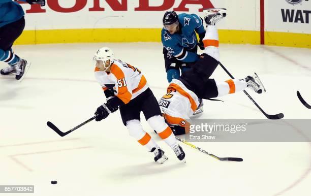 Valtteri Filppula of the Philadelphia Flyers skates away with the puck as Radko Gudas of the Philadelphia Flyers collides with Kevin Labanc of the...