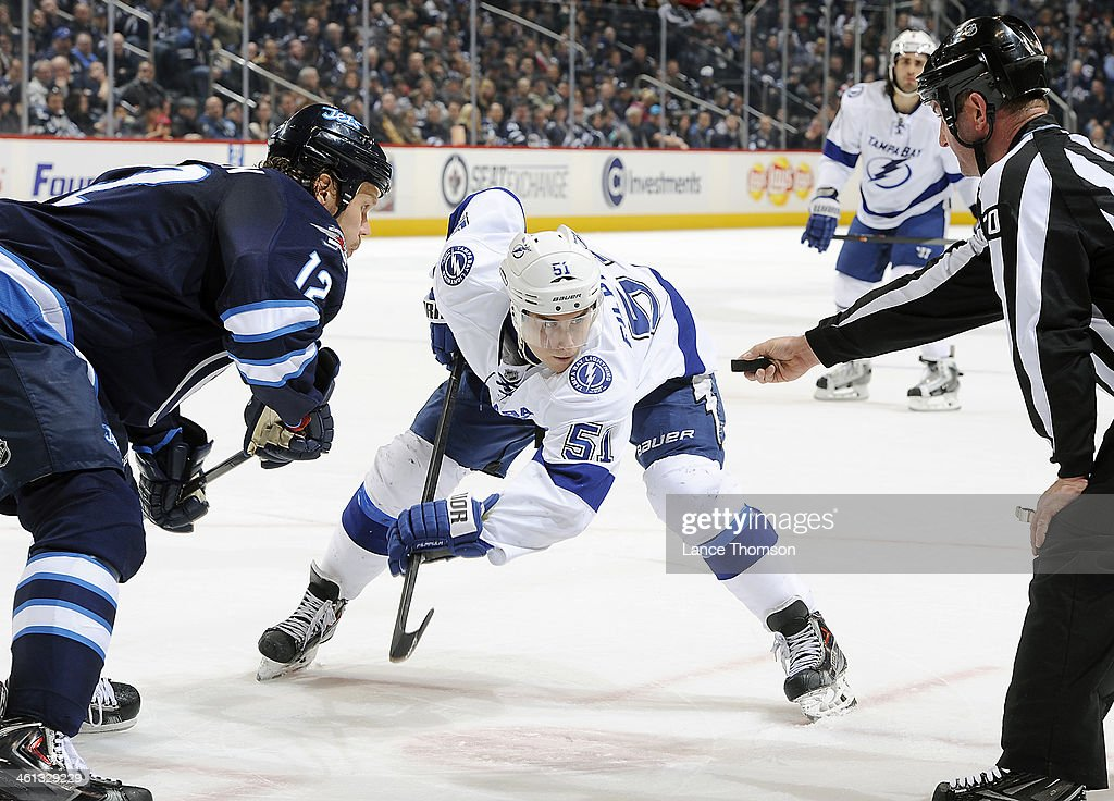 Valtteri Filppula #51 of the Tampa Bay Lightning and Olli Jokinen #12 of the Winnipeg Jets eye the puck as they wait a third period face-off at the MTS Centre on January 7, 2014 in Winnipeg, Manitoba, Canada.