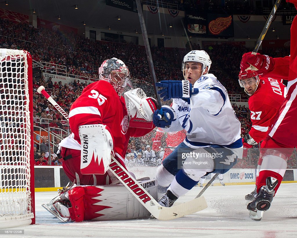 Valtteri Filppula #51 of the Tampa Bay Lightning crashes the net trying to avoid running in to Jimmy Howard #35 of the Detroit Red Wings as the puck goes into the corner during an NHL game at Joe Louis Arena on November 9, 2013 in Detroit, Michigan. Tampa Bay defeated Detroit 3-2 in OT