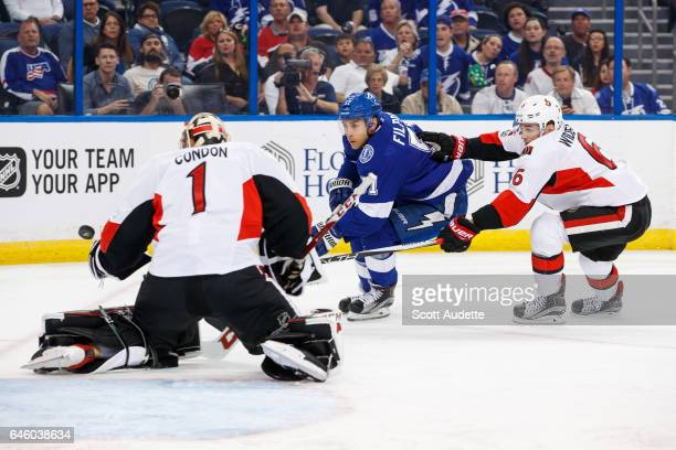 Valtteri Filppula of the Tampa Bay Lightning shoots the puck against goalie Mike Condon and Chris Wideman of the Ottawa Senators during the first...
