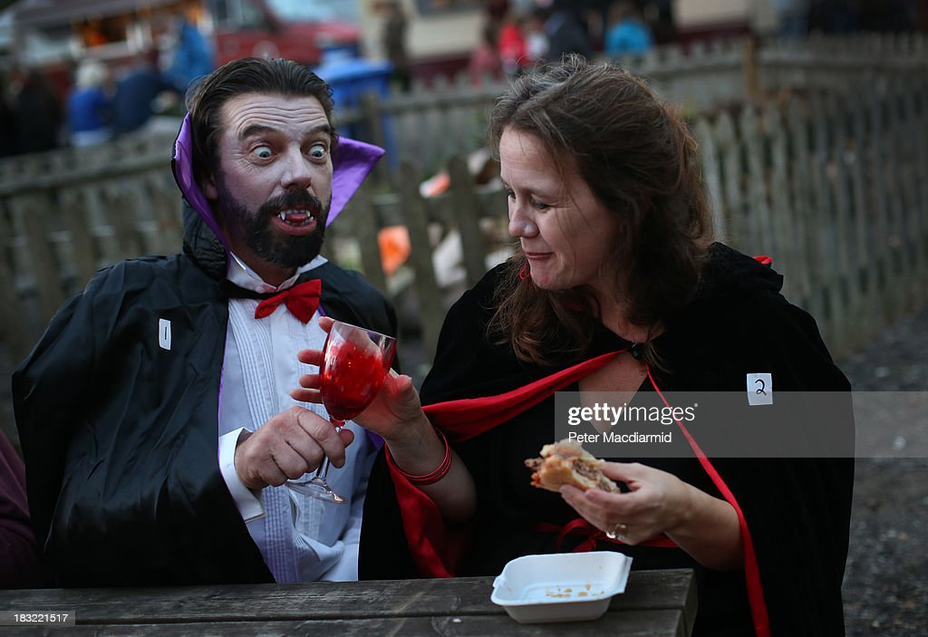 A vampire couple enjoy a drink and a burger at the Shocktober Fest at Tulleys Farm on October 5, 2013 near Crawley, West Sussex. Each October thousands attend the United Kingdom's biggest Halloween themed attraction which includes six different haunted attractions and rides. The event set a new UK record for the biggest gathering of vampires, but missed out on breaking the world record.