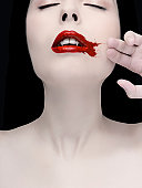 A vampire wiping blood from her mouth