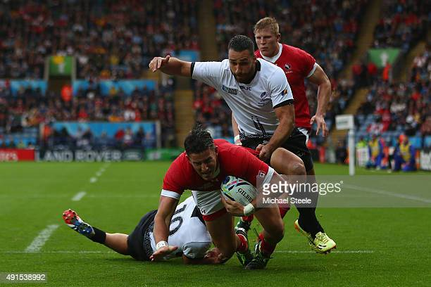 Van Der Merwe of Canada scores the opening try as Madalin Lemnanu of Romania challenges during the 2015 Rugby World Cup Pool D match between Canada...