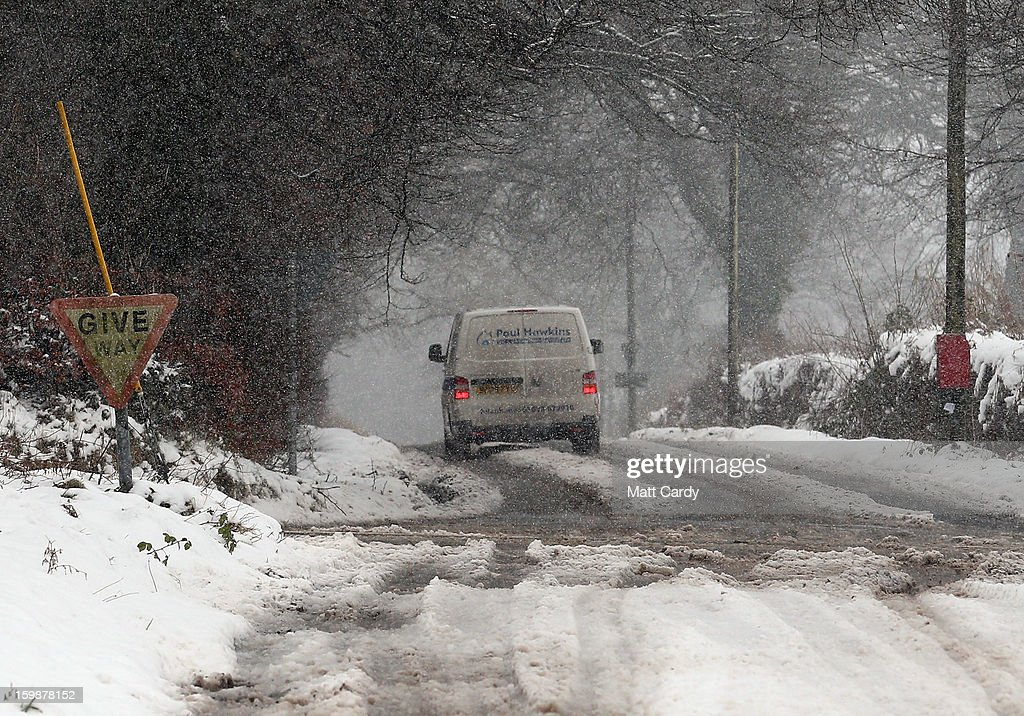 A van drives along a road as snow falls on January 22, 2013 on Exmoor, England. Snow and ice is continuing to cause disruption to some parts of the UK with more snow forecast for the South West tonight.