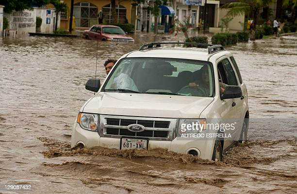 A van drives in a flooded street following the passage of Jova Hurricane in the region in Manzanillo Colima State Mexico on October 12 2011 Jova lost...