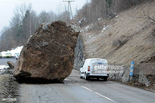 A van drives past a huge rock that fell on February 27 onto the RD117 road leading to the ski resorts of Moutiers Les Menuires and Val Thorens in the...