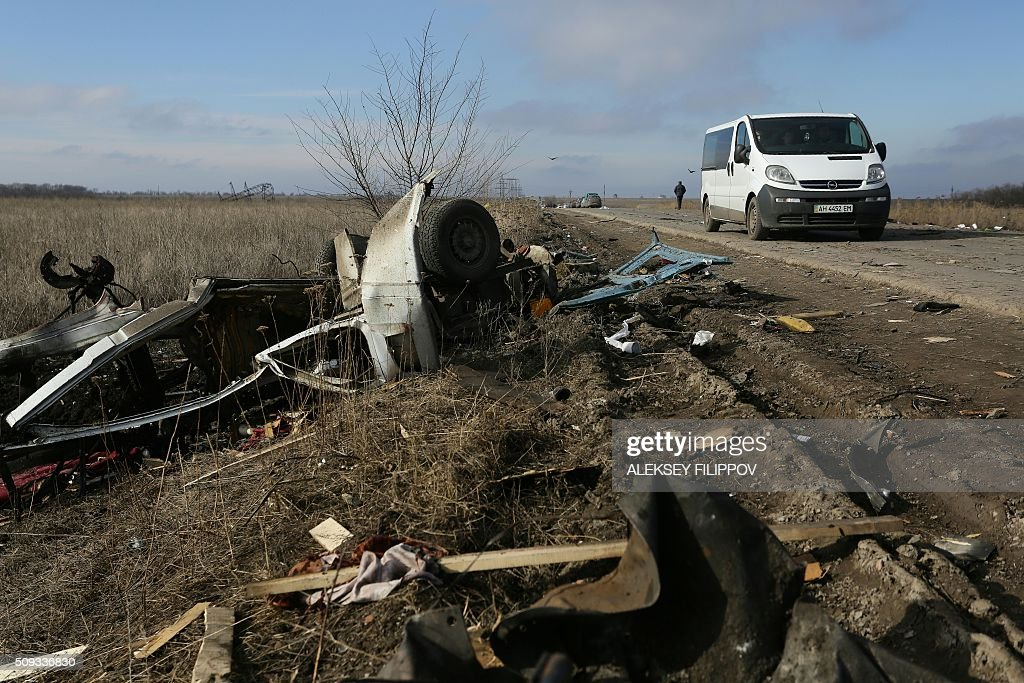 A van drives past the debris of a passenger minibus after it hit a mine near Marinka on February 10, 2016. Three people were killed on February 10 when a passenger minibus hit a mine in separatist eastern Ukraine during a relative calm in fighting in the 21-month war. / AFP / ALEKSEY FILIPPOV
