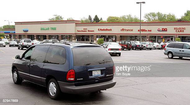 A van drives through the parking lot of a shopping strip mall May 18 2005 in Palatine Illinois Strip malls have become a prominent suburban feature...