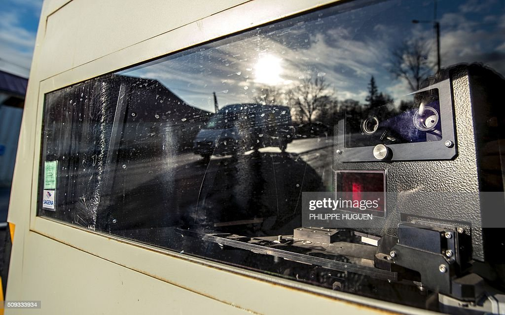 A van is reflected in a speed camera on the D939 in Aubigny-en-Artois on February 10, 2016, in the first area in France to be outfitted with 'luring signs'. Eleven signs reading 'For your safety, frequent use of speed cameras' will be installed on a portion of the by-road in the Pas-de-Calais department, but a speed camera will be hidden behind only one of the signs, which will be moved regularly. / AFP / PHILIPPE HUGUEN