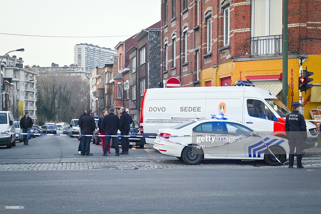 A van of the Belgian Army Mine Clearance Department (SEDEE/DOVO) and a police car (R) are parked on March 26, 2013 inside the security perimeter at the Courtoisie street (Hoffelijkheidsstraat) in Anderlecht, Brussels, which was evacuated for suspicion of explosive in a house where lived a man killed earlier today on the highway A8 Lille - Tournai - Brussels in Meslin L'Eveque (Ath) after a chase while Belgian federal police tried to intercept him. The victim alledgedly committed a hold-up in Anderlecht on March 21. Belgium Out