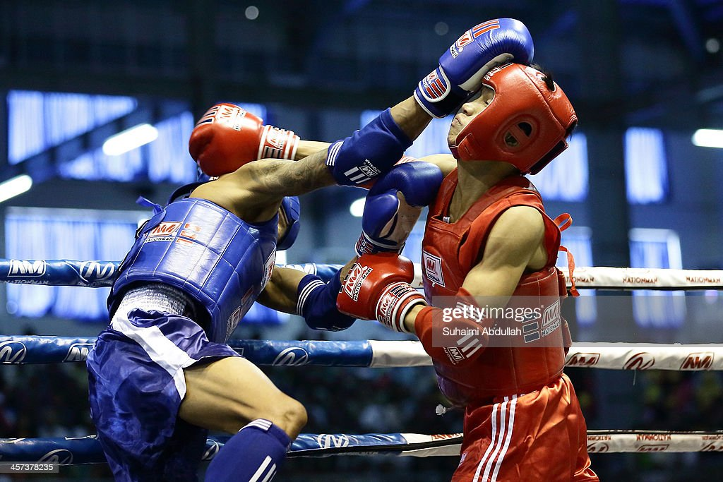 Van Tu Le (red) of Vietnam fights Bouaphan Phankeo (blue) of Laos during the male muay 54kg division weight bout at the Wunna Theikdi Boxing Centre during the 2013 SEA Games on December 17, 2013 in Nay Pyi Taw, Burma.