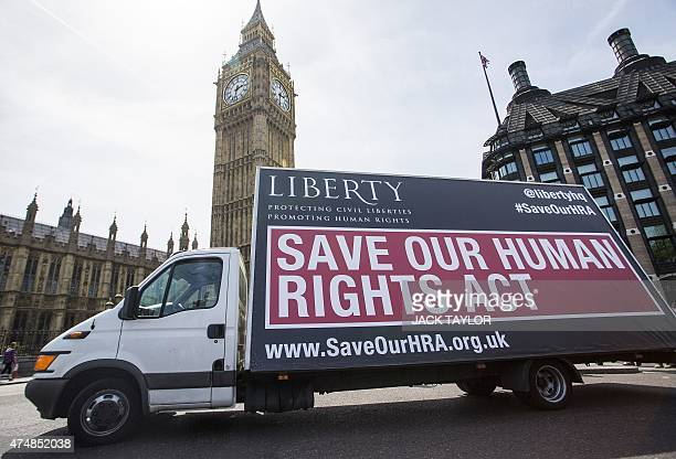 A van with a sign calling on the British government to 'Save Our Human Rights Act' is pictured as it is driven past the Houses of Parliament in...