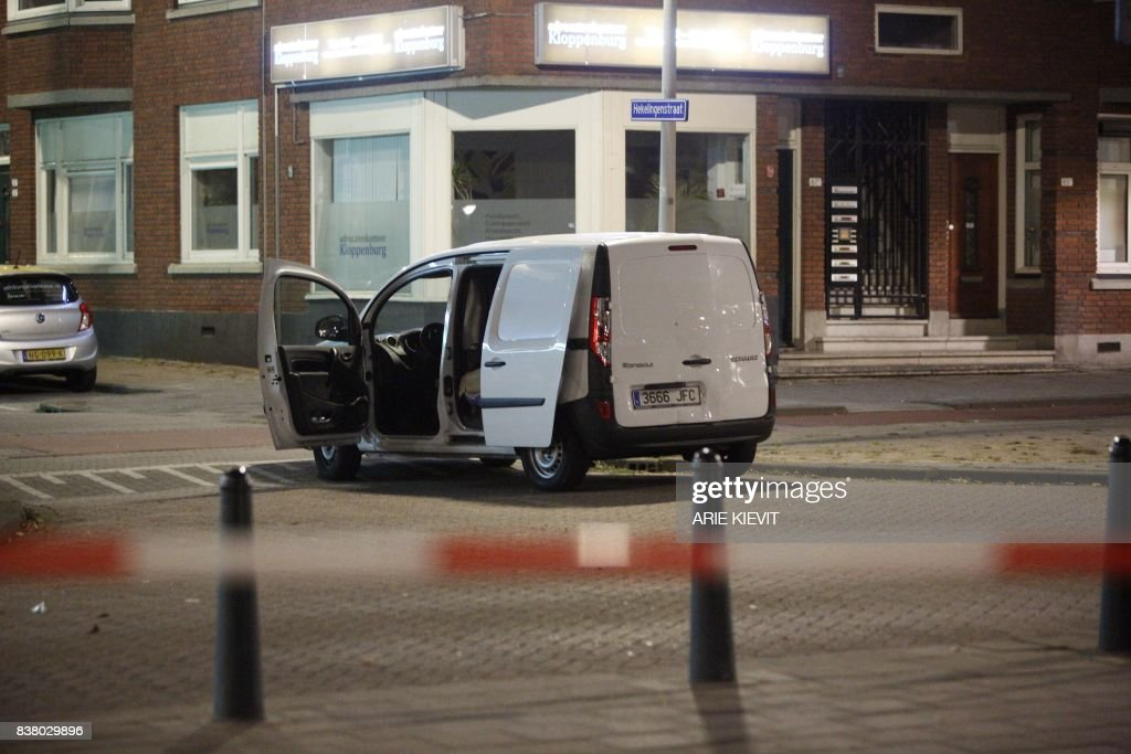 TOPSHOT - A van with a Spanish numberplate near the concert venue Maassilo is seen during police investigations after a rock concert was cancelled due to a terror threat, in Rotterdam, The Netherlands, on August 23, 2017. A rock concert in Rotterdam was cancelled on August 23 due to a terror threat involving a Spanish van found with gas bottles inside, the local mayor said. Earlier the Maassilo venue announced that 'due to a terrorist threat, the Allah-Las concert will not take place this evening, on police orders'. Rotterdam police confirmed the decision was taken due to a 'possible terrorist threat' and that the van's driver had been arrested. / AFP PHOTO / ANP / Arie Kievit / Netherlands OUT