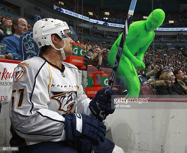 Vancouver Canuck fan wears a green body suit as he taunts Francis Bouillon of the Nashville Predators as he sits in the penalty box during their game...