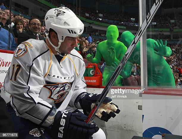 Vancouver Canuck fans wear green body suits as they taunt David Legwand of the Nashville Predators as he sits in the penalty box during their game...