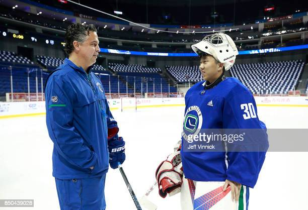 Vancouver Canucks backup goaltender Zehao Sun talks to head coach Travis Green of the Vancouver Canucks during their gameday skate at MercedesBenz...