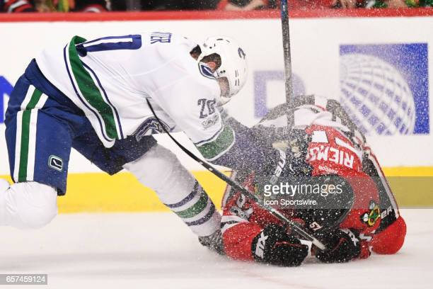 Vancouver Canucks center Brandon Sutter falls into Chicago Blackhawks defenseman Trevor van Riemsdyk after clearing the puck in the second period...