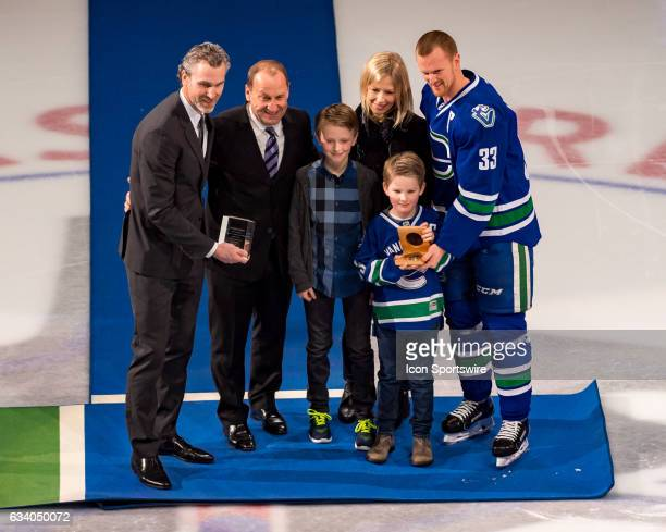 Vancouver Canucks Center Henrik Sedin stands with his family as he's presented gifts from Trevor Linden and Stan Smyl for scoring 1000 points prior...