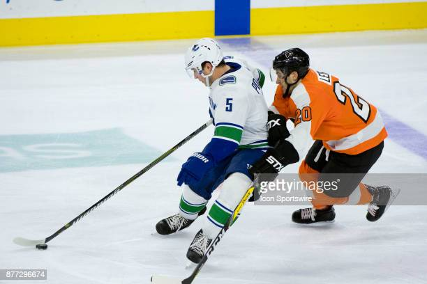 Vancouver Canucks Defenceman Derrick Pouliot keeps the puck from Philadelphia Flyers Left Wing Taylor Leier in the third period during the game...