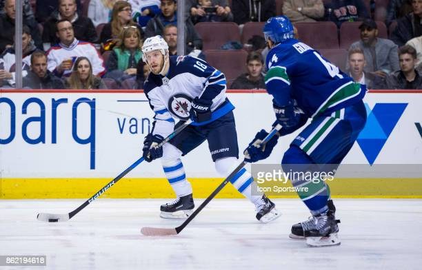 Vancouver Canucks Defenceman Erik Gudbranson attempts to check Winnipeg Jets Center Bryan Little in a NHL hockey game on October 12 at Rogers Arena...