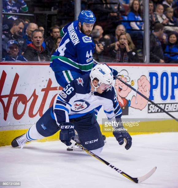 Vancouver Canucks Defenceman Erik Gudbranson checks Winnipeg Jets Left Wing Marko Dano in a NHL hockey game on October 12 at Rogers Arena in...