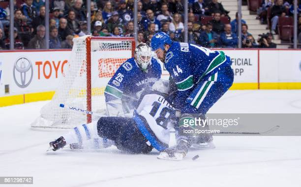 Vancouver Canucks Defenceman Erik Gudbranson checks Winnipeg Jets Center Bryan Little to the ice in front of Vancouver Canucks Goalie Jacob Markstrom...