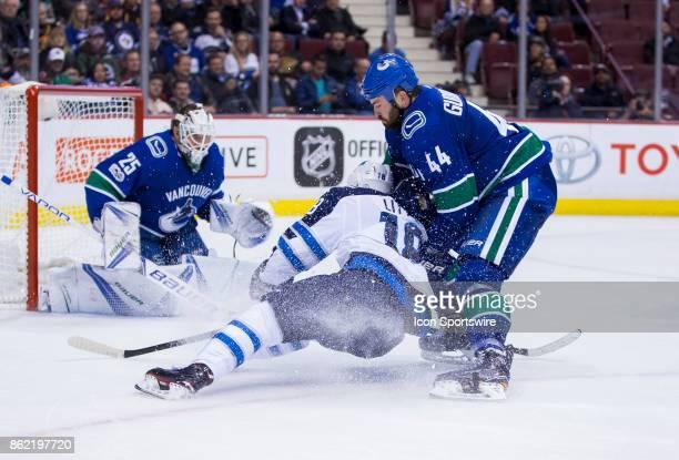 Vancouver Canucks Defenceman Erik Gudbranson checks Winnipeg Jets Center Bryan Little in front of Goalie Jacob Markstrom in a NHL hockey game on...